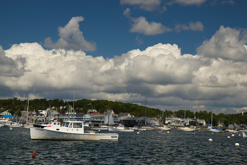 "Boothbay Harbor, August 22, 2011, 11:12 am<br /> <br /> When considering taking up photography several years ago, I picked up Scott Kelby's classic ""The Digital Photography Book."" On landscape photography, he advises shooting at only two times of the day, sunrise and sunset. He says that some nature magazine editors will not consider landscape work that is not shot at these two times.<br /> <br /> This rule has a sound basis-the warm light in the early morning hours or during sunsets is ideal rather than the generally harsh light in between. However, like many rules, it is meant to be broken. I think this was the case when I took this photo at around 11 am, capturing the gorgeous deep blue sky and cotton candy, marshmallow-like clouds. f6.3, 1/320, 100 ISO, 46 mm (74 mm with 1.6X crop factor)."