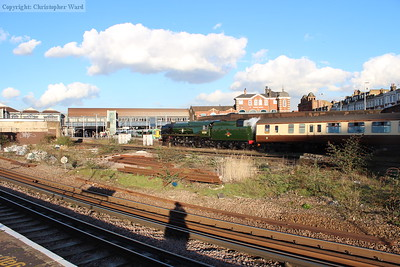 The sunshine (a rare commodity after the wettest winter on record) comes out to record 35028 passing Clapham Junction, with the imposing Brighton Yard entrance building looming over the scene