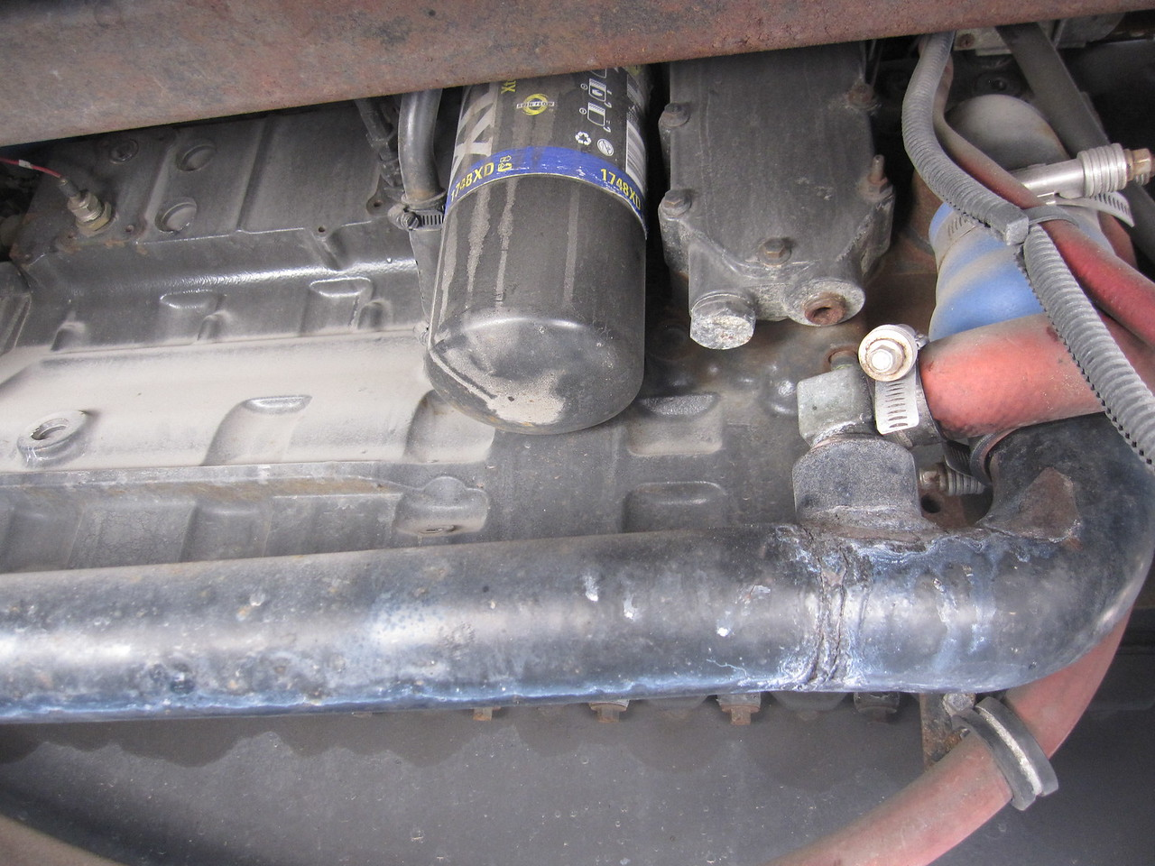 """Several years of coolant drips leave silicate residue on the bottom of this pipe.  It connects the engine water jacket to the radiator.  Two """"take off"""" connections are part of this pipe.  One runs to the filler/expansion tank (shown) and the other runs forward to the dash heat exchanger (out of photo)."""