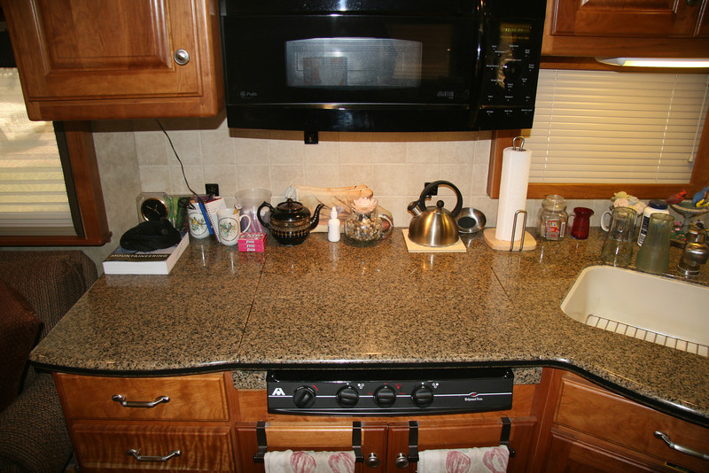 Kitchen counter area with stove top closed by corian panels.  Using the stove requires removing these panels.  As a result, general purpose counter space is lost.