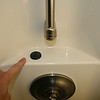 A second proximity switch is mounted in the center of this shelf (under fiberglass).  The black disk is a magnet which can be slid over the switch to stop/start water flow.  This one is easy to access when standing in the shower stall.  No holes have been drilled.