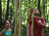 HOLLY PELCZYNSKI - BENNINGTON BANNER Music educator and drummer Brian DeAngelo hangs large tree limbs while making a natural wind-chime, as student Sophie Kaufer, 10 years old watches apprehensively on Friday  morning at the The George Aiken Wildflower Trail during The Vermont Art's Exchange Make Art, Make Noise! Camp at the Bennington Museum.
