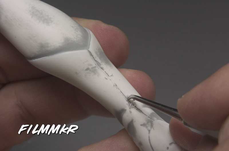 Break out a scriber and gently, CAREFULLY re-scribe the seam that runs down the back of her calf.