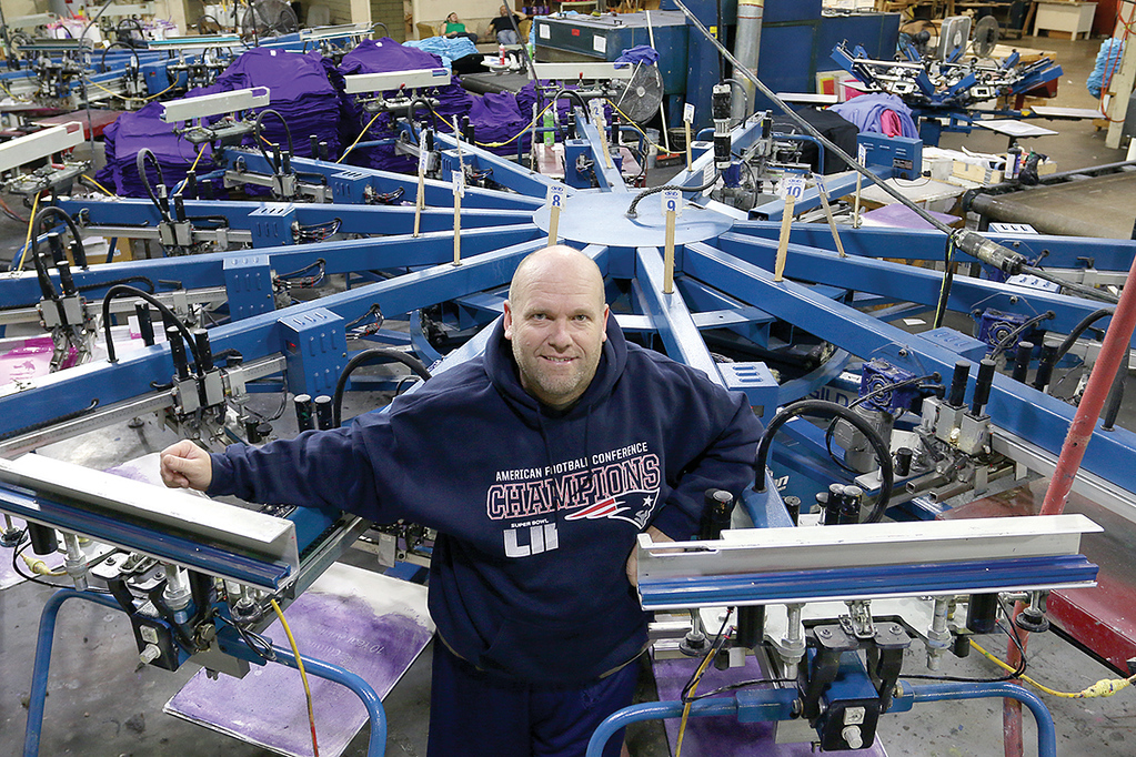 . Owner of Bay State Apparel in Leominster Brian Whitney, wearing one of the American Football Conference Champion shirts they had made just after the Patriots last win, stand near they 12 color automatic printer, one of two, that will be printing Super Bowl shirts if they win this Sunday. SENTINEL & ENTERPRISE/JOHN LOVE