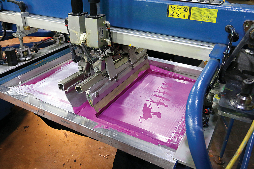 . The 12 color automatic printer at Bay State Apparel works on  making some t-shirts on Tuesday in their facility in Leominster. It is putting some pink onto a shirt. This is one of two machine that will be making some of the Patriots Super Bowl shirts if they win on Sunday. SENTINEL & ENTERPRISE/JOHN LOVE