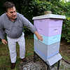 Michael Fontaine takes about bees and how he collects honey from all his hives on Friday afternoon at his home in Leominster. This hive he said hold 80,000 bees. SENTINEL & ENTERPRISE/JOHN LOVE