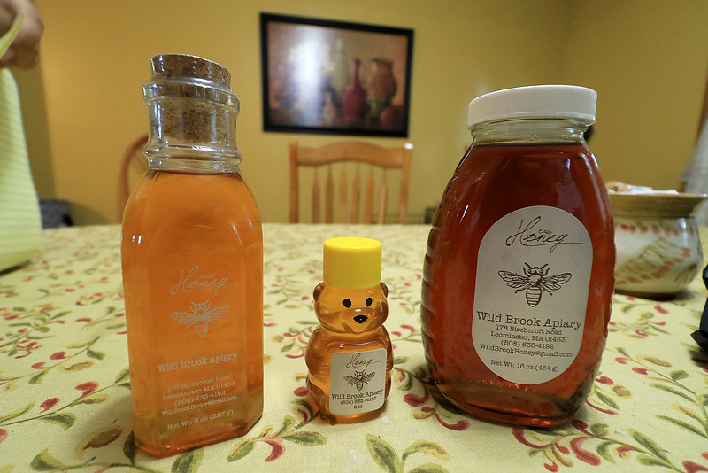 Michael Fontaine takes about bees and how he collects honey from all his hives on Friday afternoon at his home in Leominster. These are the three bottles that he sells his honey in. SENTINEL & ENTERPRISE/JOHN LOVE