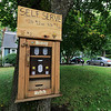 Michael Fontaine takes about bees and how he collects honey from all his hives on Friday afternoon at his home in Leominster. He sells some of his honey in this box attached to the tree in the front yard. SENTINEL & ENTERPRISE/JOHN LOVE