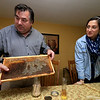 Michael Fontaine takes about bees and how he collects honey from all his hives on Friday afternoon at his home in Leominster. Here he shows off a honeycomb and next to him is his daughter Sarah Fontaine. SENTINEL & ENTERPRISE/JOHN LOVE