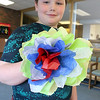 Crafter June Celona made Mexican tissue paper flowers with the kids at the Fitchburg Public Library on Tuesday afternoon. Joshua Hale, 9, shows off the flower he made during the crafting hour. SENTINEL & ENTERPRISE/JOHN LOVE