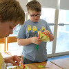 Crafter June Celona made Mexican tissue paper flowers with the kids at the Fitchburg Public Library on Tuesday afternoon. Timothy Johnson, 10 in glasses, and Walter Johnson, 11, work on making flowers during the crating hour. SENTINEL & ENTERPRISE/JOHN LOVE