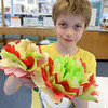 Crafter June Celona made Mexican tissue paper flowers with the kids at the Fitchburg Public Library on Tuesday afternoon. Walter Johnson, 11, the two flower he made during the crafting hour. SENTINEL & ENTERPRISE/JOHN LOVE