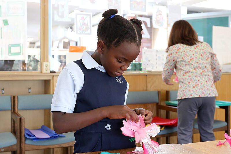 Crafter June Celona made Mexican tissue paper flowers with the kids at the Fitchburg Public Library on Tuesday afternoon. Working on her flower is Bonta Piazza, 7, during hte crafting hour at the library. SENTINEL & ENTERPRISE/JOHN LOVE