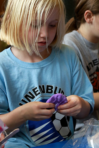 The Lunenburg Public Library had a slime making event for the kids on Wednesday morning. Norah Brown, 8, uses her hands to mix up her slime ingredients during the program at the library. SENTINEL & ENTERPRISE/JOHN LOVE