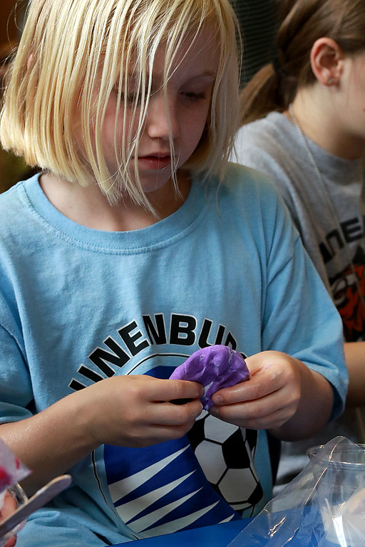 . The Lunenburg Public Library had a slime making event for the kids on Wednesday morning. Norah Brown, 8, uses her hands to mix up her slime ingredients during the program at the library. SENTINEL & ENTERPRISE/JOHN LOVE