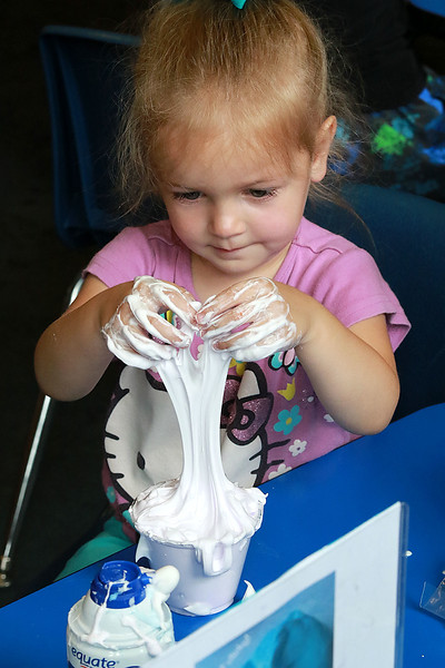 The Lunenburg Public Library had a slime making event for the kids on Wednesday morning. Jovienne Dionne, 3, of Fitchburg mixes up her slime using her hands during the program at the library. SENTINEL & ENTERPRISE/JOHN LOVE