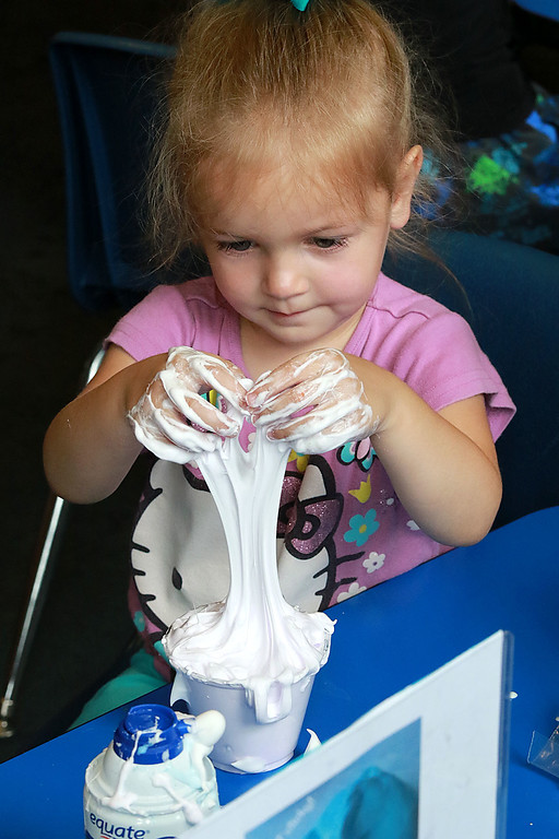 . The Lunenburg Public Library had a slime making event for the kids on Wednesday morning. Jovienne Dionne, 3, of Fitchburg mixes up her slime using her hands during the program at the library. SENTINEL & ENTERPRISE/JOHN LOVE
