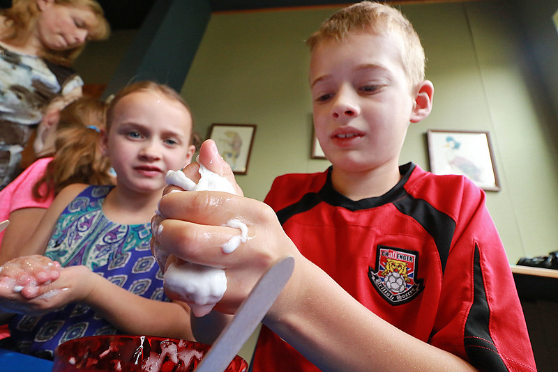 The Lunenburg Public Library had a slime making event for the kids on Wednesday morning. Colby Goulding, 8, uses his hands to mix up his slime ingredients as Sophie Goulding, 6, looks on while she mixes her with her hands. SENTINEL & ENTERPRISE/JOHN LOVE