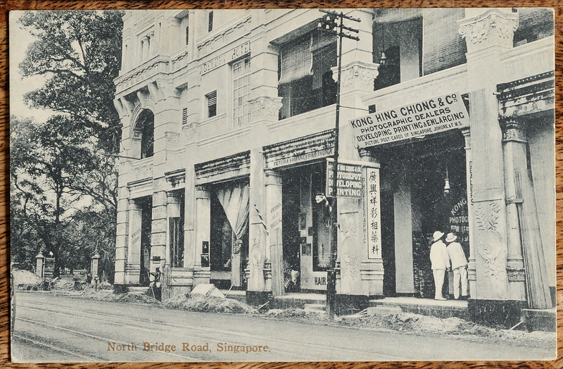 Picture postcard showing shop of publisher Kong Hing Chiong & Co. on 104 North Bridge Road in the Adelphi Hotel building