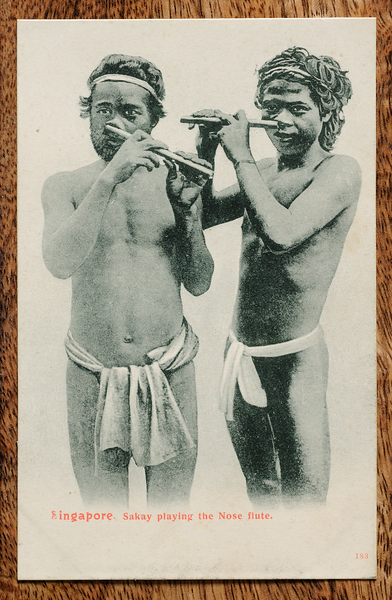 Picture postcard of orang asli playing indigenous nose flute, published by Max Hilckes