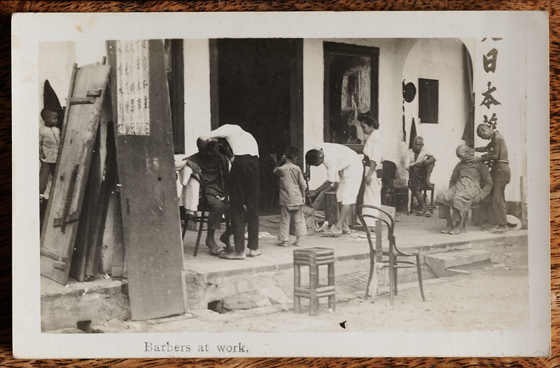 Postcard showing barbers at work, published by the Federal Rubber Stamp Company, Malaya.