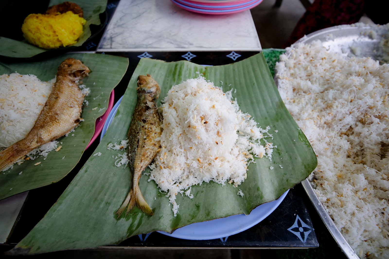 A fried fish is served on the side of every small mound of coconut shred filled rice