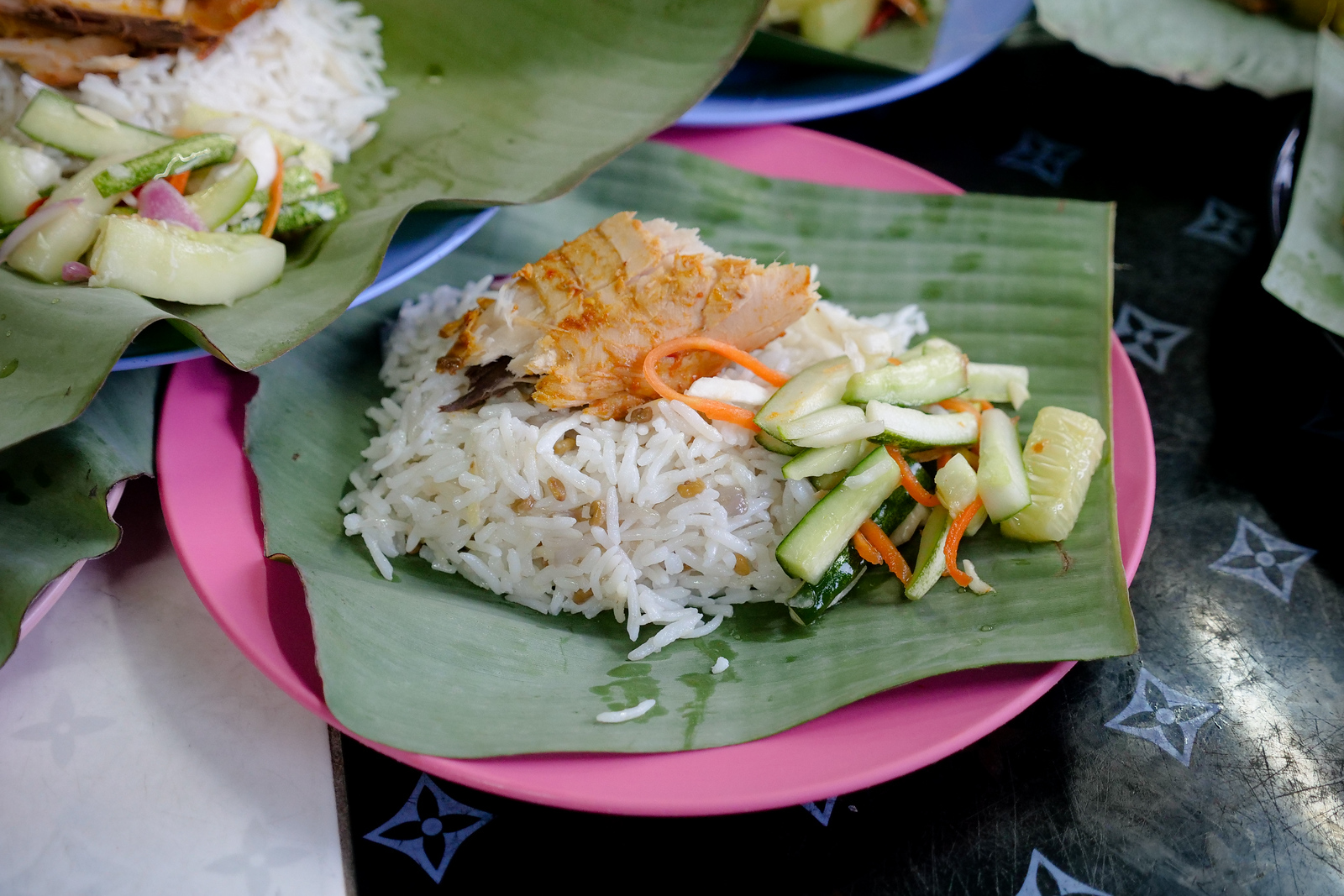 A simple combination of fish over rice, served with a sour cucumber and soft carrot combo