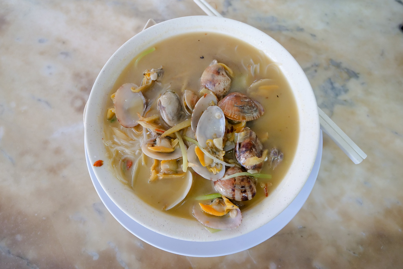 Thin white rice noodles and a huge amount of fresh clams. The soup broth is incredible, and packed with chilies garlic and ginger