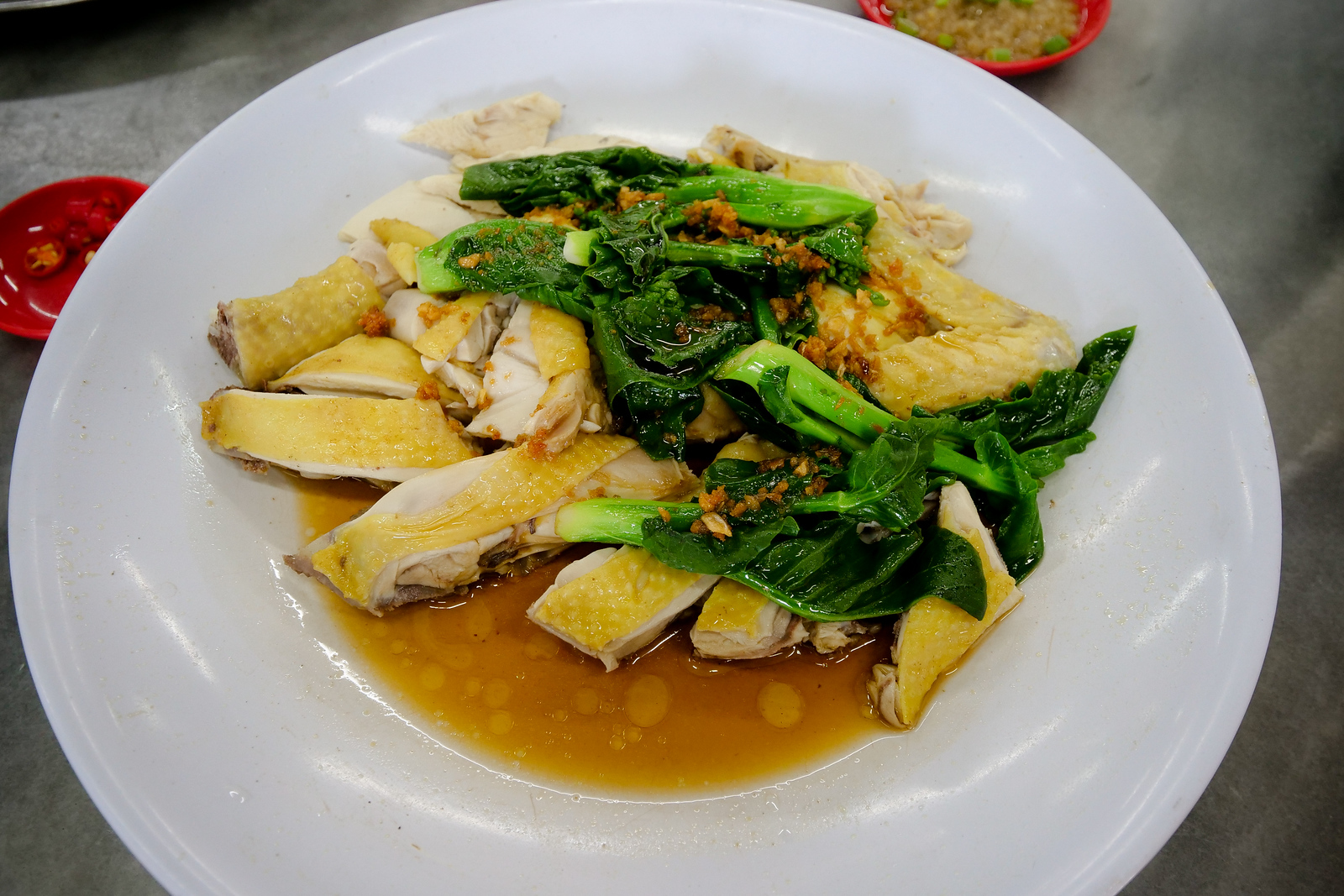 Serving the yellow skin chicken with chinese kale and fried garlic, this dish makes an excellent food to pair with your steam fish head