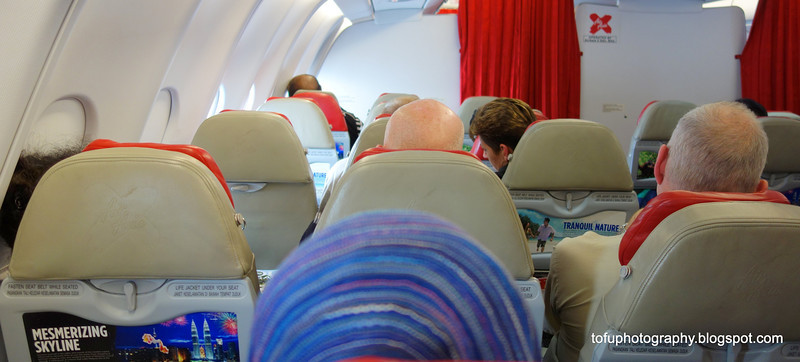 On an aircraft on the way to Kuala Lumpur, Malaysia in September 2012. The woman in front is wearing a hijab