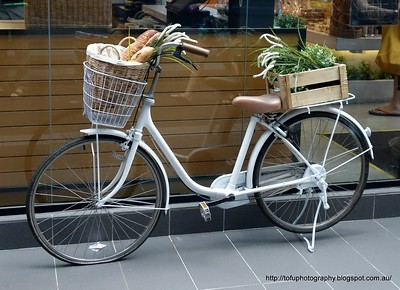 A hipster bicycle with basket and rear pannier filled with bread and vegetables a la Provence style parked outside a shop in Kuala Lumpur, Malaysia in August 2017