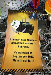A big banner in the atrium of a shopping centre in Kuala Lumpur, Malaysia in August 2017. Standby! your mission: Operation escalator upgrade. Completed by September 2017. We shall not fail!