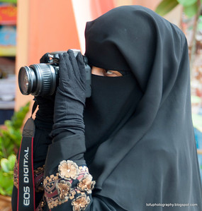 Woman taking a photo at the Oriental Village, Langkawi, Malaysia, in June 2011