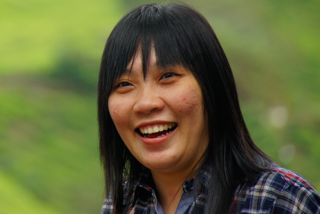 A lady smiles outside the Boh Tea factory - Cameron Highlands, Malaysia.  Travel photo from Cameron Highlands, Malaysia.