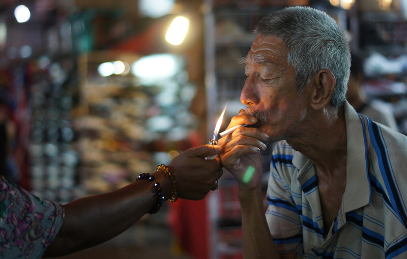 "<a href=""http://nomadicsamuel.com/photo-blog/man-smoking-petaling-street-kuala-lumpur-malaysia-travel-photo"">http://nomadicsamuel.com/photo-blog/man-smoking-petaling-street-kuala-lumpur-malaysia-travel-photo</a> : Today's daily travel photo is of a man smoking as pedestrians pass by him on busy Petaling Street market at night - Kuala Lumpur, Malaysia."