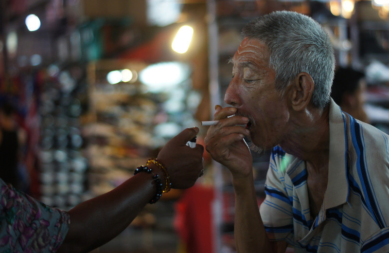 This travel photo is of a shot of a Malaysian man just about to smoke a cigarette at the Petaling night market located in Chinatown Kuala Lumpur, Malaysia.