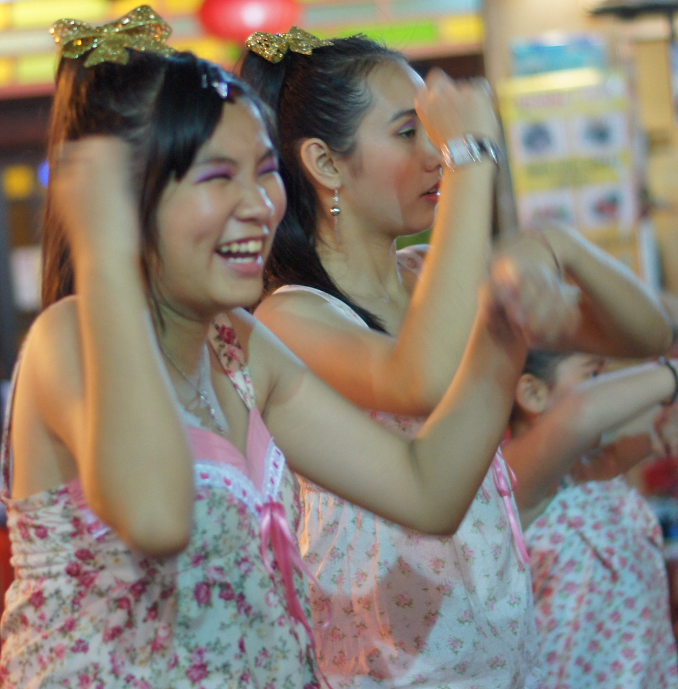 A candid shot of some girls laughing while performing a dance.  These girls really were enjoying putting on a show.