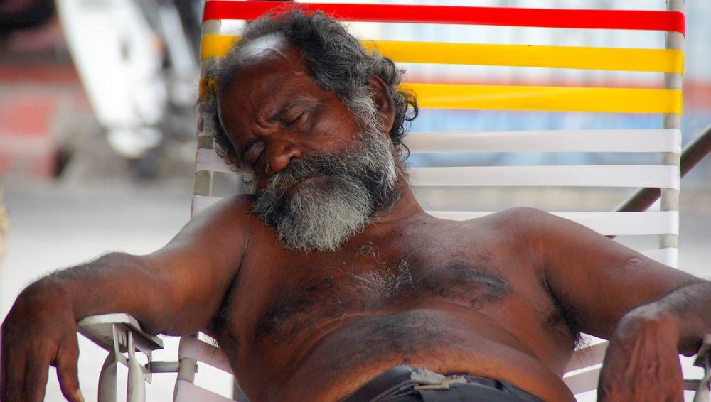 Malaysian man sleeping on a lawn chair in Penang, Malaysia