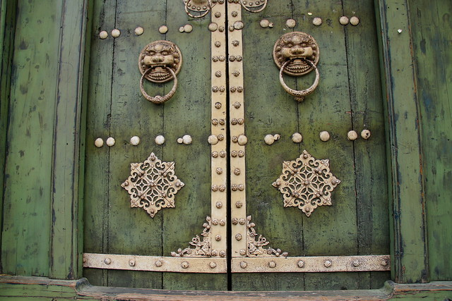 Ornate gate with lion door handles