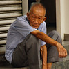 This is a travel photo of a candid shot I took of an elderly man with a distinct face sitting on a curb of a bustling street in Kuala Lumpur, Malaysia.