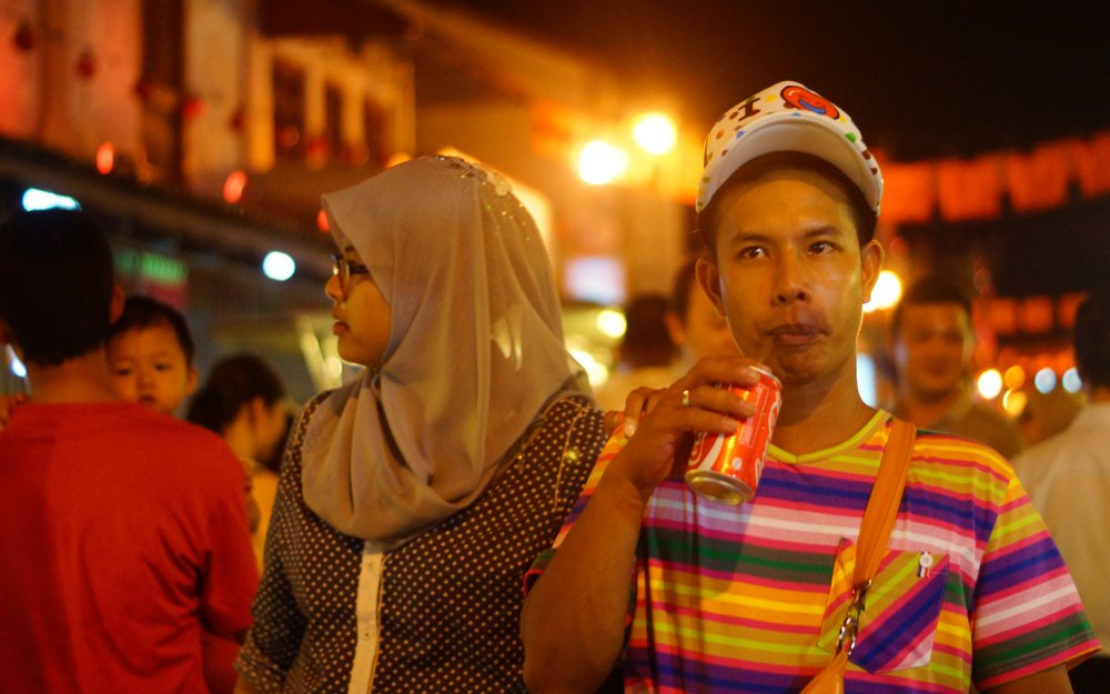 A man strolls down the main strip of the night market enjoying a refreshment along the way.