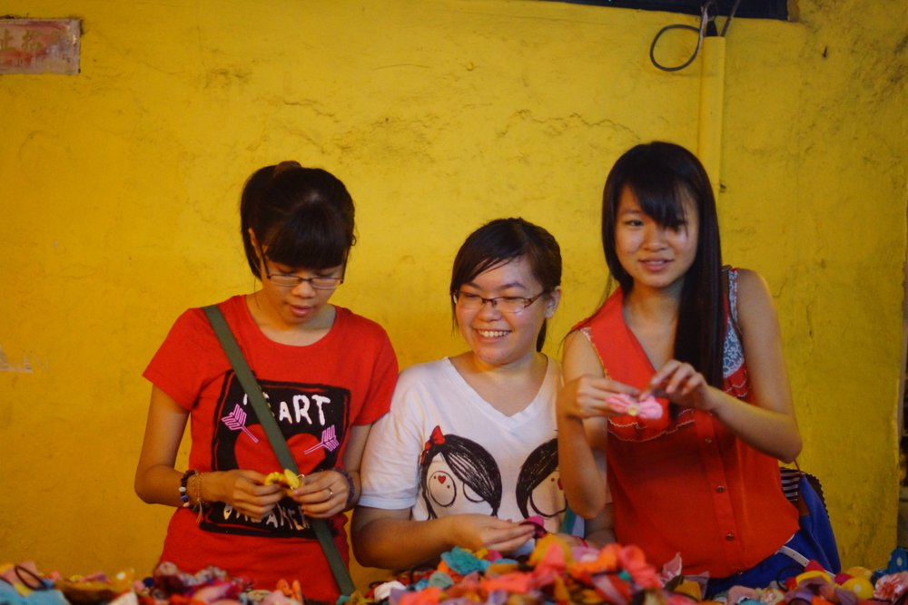 A group of ladies flash a candid smile while enjoying shopping at the night market for various kinds of trinkets.