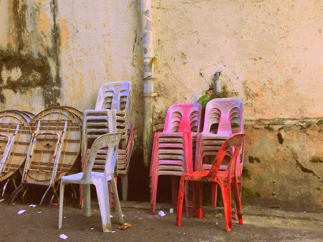 Plastic chairs and tables stacked against a wall