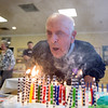 Leominster native Malcolm Brown takes a deep breath and swiftly blows out 100 candles at his 100th birthday celebration at the Veterans Memorial Center in Leominster on Sunday April 9, 2017.  (Sentinel & Enterprise photo/Jeff Porter)