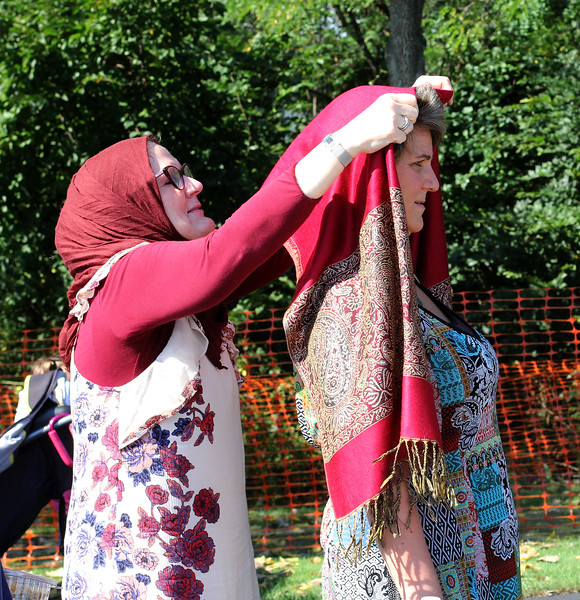 Malden, Ma. 9-17-17. Sarah Quaderi, left, helps Deborah Goldman try on a Hijab at the Try-on Hijab counter at the second annua Malde-Muslim festival.