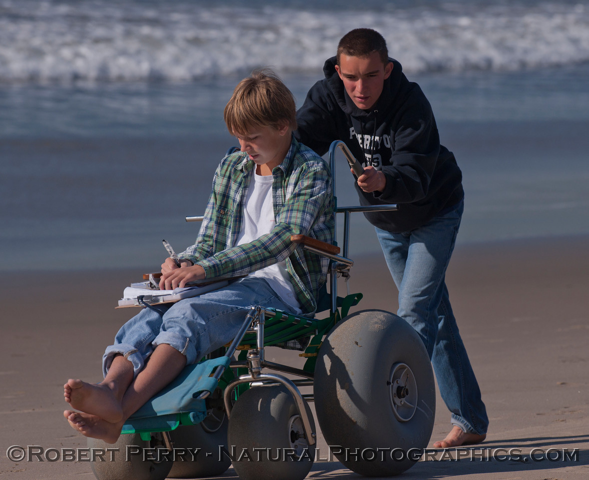 Student researcher in sand wheelchair on load from LA County Malibu Lifeguard HQ.