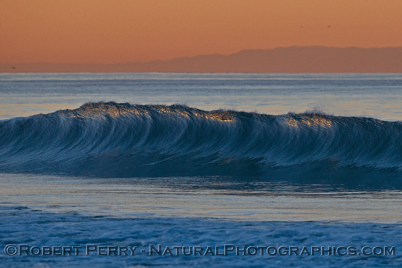 A beautiful glassy wave with an orange peel texture is photographed at dawn with Catalina Island in the background.