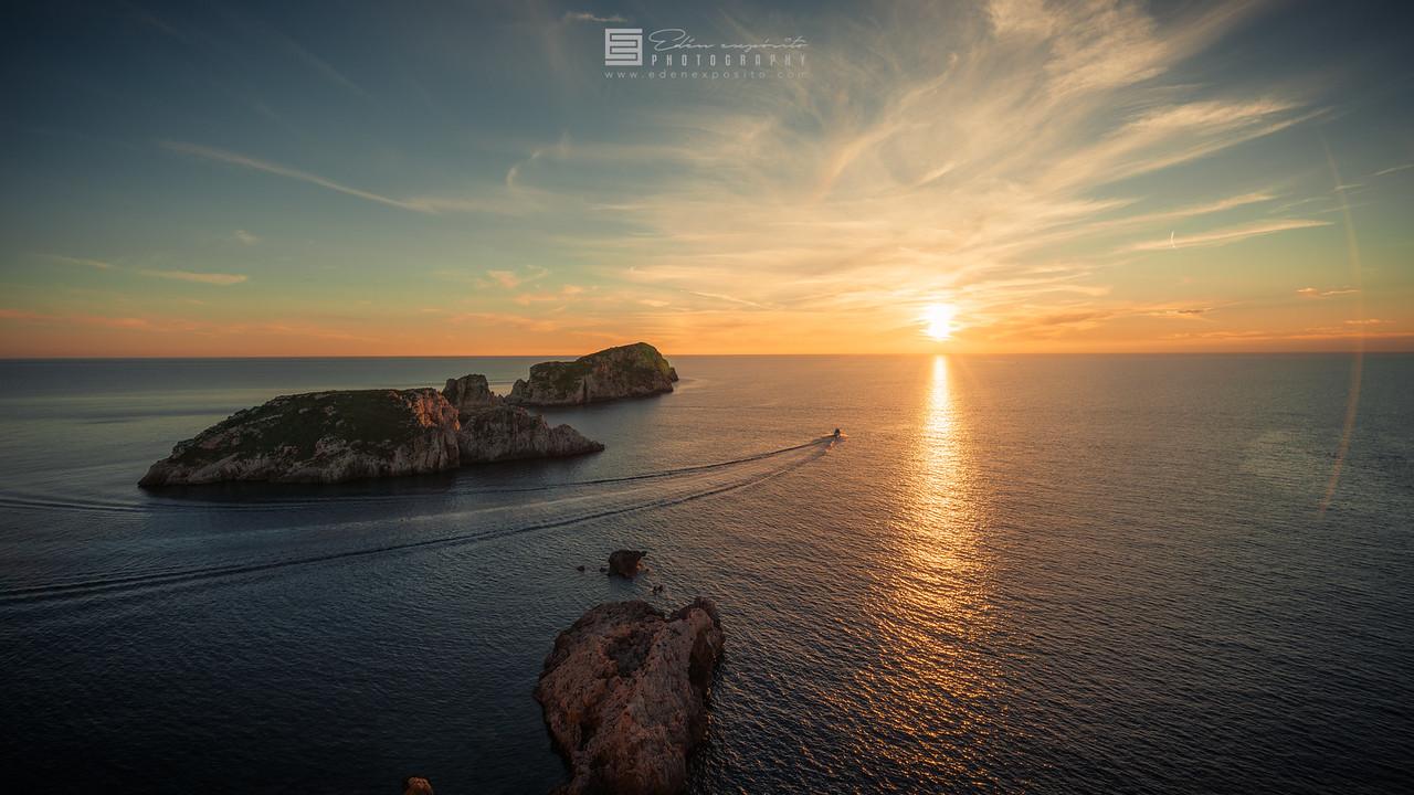 Boat go to sunset at Es Malgrats islands Mallorca coastline