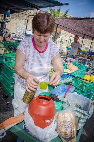 A Maltese woman selling capers at the Sunday Market - Marsaxlokk, Malta