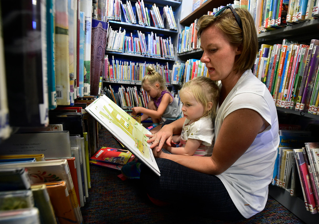 . BROOMFIELD, CO - SEPTEMBER 13 2018 Megan Lueblke reads to her daughter Emma, 2, while her daughter Kaylie, 4, searches for books in the Mamie Doud Eisenhower Library in Broomfield on Thursday September 13, 2018.  For more photos go to broomfieldenterprise.com (Photo by Paul Aiken/Staff Photographer)